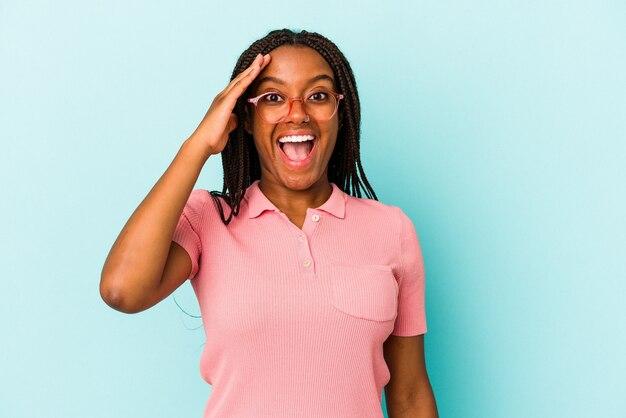 La giovane donna afroamericana isolata su fondo blu grida forte, tiene gli occhi aperti e le mani tese.