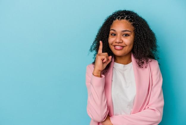 Giovane donna afroamericana isolata su fondo blu che mostra il numero uno con il dito.