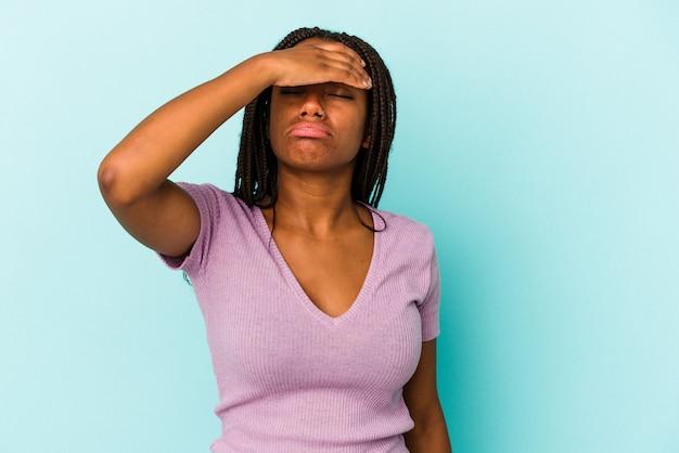Giovane donna afroamericana isolata su sfondo blu toccando le tempie e avendo mal di testa.