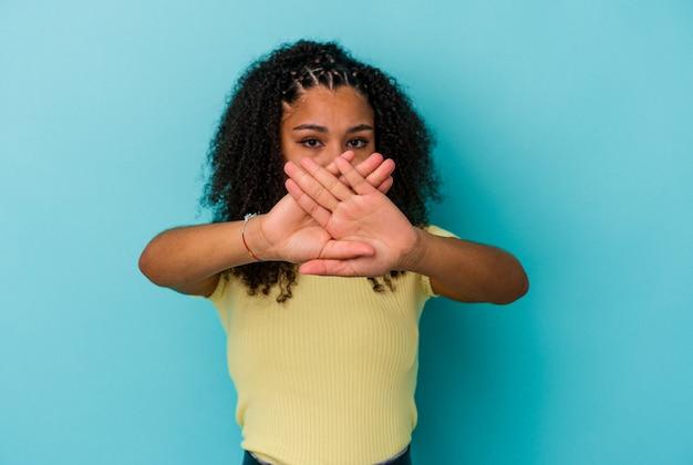 Giovane donna afroamericana isolata sulla parete blu che fa un gesto di diniego