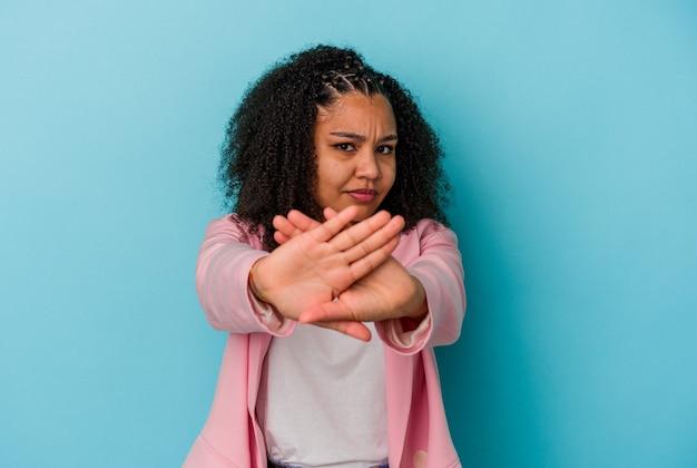Giovane donna afroamericana isolata sulla parete blu in piedi con la mano tesa che mostra il segnale di stop, impedendoti