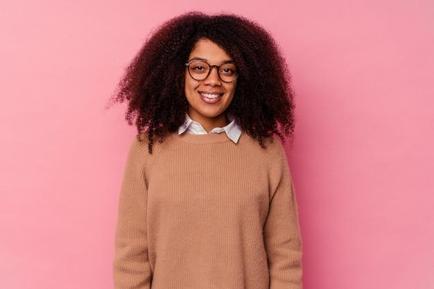 Giovane donna afroamericana isolata su sfondo rosa felice, sorridente e allegra.