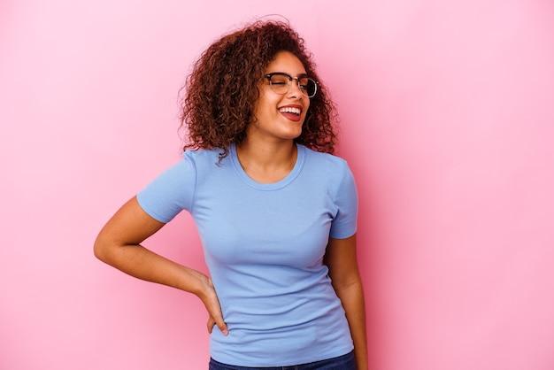 La giovane donna afroamericana isolata su sfondo rosa ride e chiude gli occhi, si sente rilassata e felice.