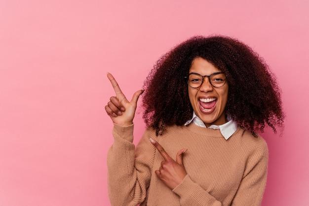 Giovane donna afroamericana isolata su sfondo rosa che indica con l'indice uno spazio di copia, esprimendo eccitazione e desiderio.