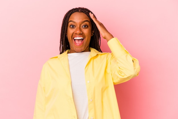 La giovane donna afroamericana isolata su fondo rosa grida forte, tiene gli occhi aperti e le mani tese.