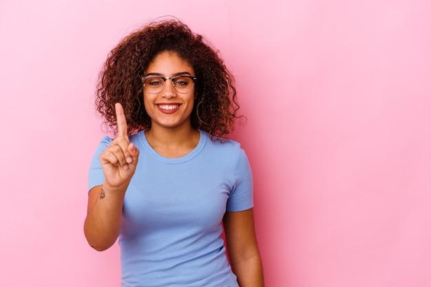 Giovane donna afroamericana isolata su sfondo rosa che mostra il numero uno con il dito.
