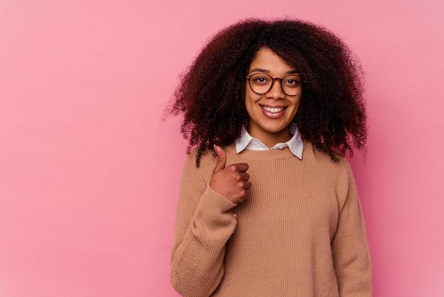 Giovane donna afroamericana isolata su fondo rosa che sorride e che alza pollice su