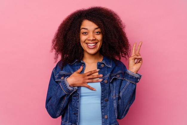 Giovane donna afroamericana isolata su sfondo rosa prestando giuramento, mettendo la mano sul petto.