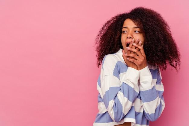 Giovane donna afroamericana isolata su fondo rosa premurosa che guarda ad uno spazio della copia che copre la bocca con la mano.
