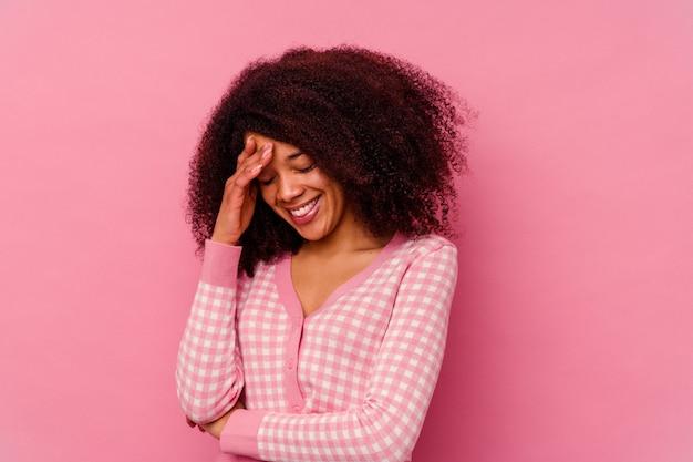 Giovane donna afroamericana isolata sul rosa che lampeggia tra le dita, imbarazzata che copre il viso.