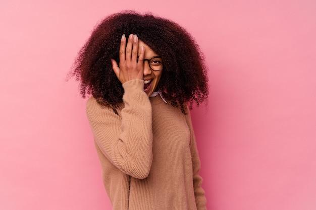 Giovane donna afroamericana isolata sul rosa divertendosi coprendo metà del viso con il palmo.