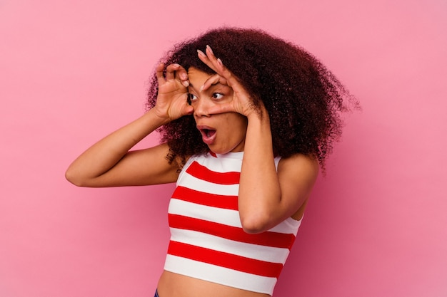 Giovane donna afroamericana isolata sul rosa tenendo gli occhi aperti per trovare un'opportunità di successo.