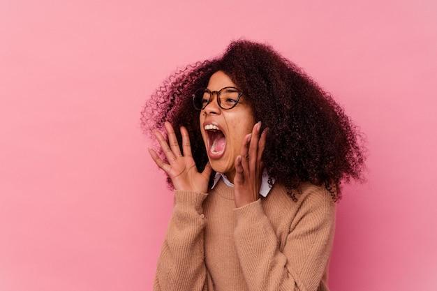 La giovane donna afroamericana isolata sul rosa grida forte, tiene gli occhi aperti e le mani tese.