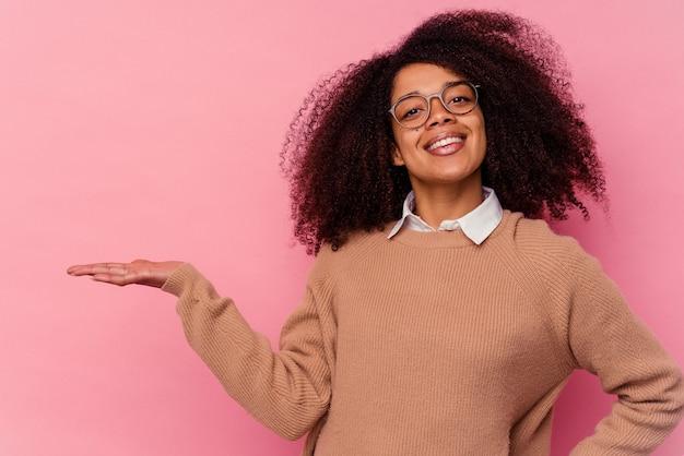 Giovane donna afroamericana isolata sul colore rosa che mostra uno spazio della copia su una palma e che tiene un'altra mano sulla vita.