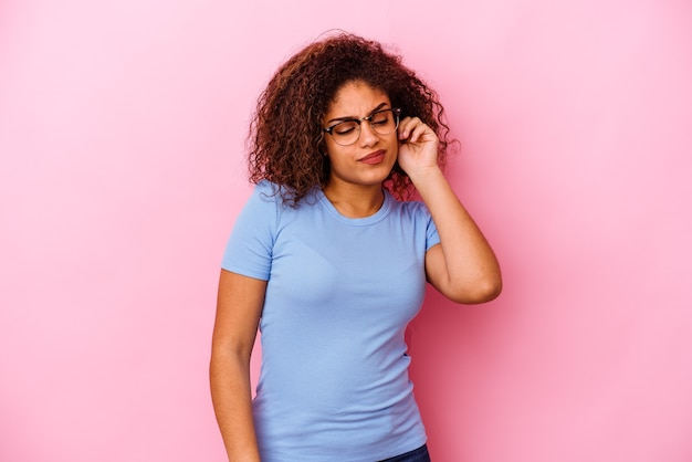 Giovane donna afroamericana isolata sul muro rosa che copre le orecchie con le dita, stressata e disperata da un ambiente rumoroso.