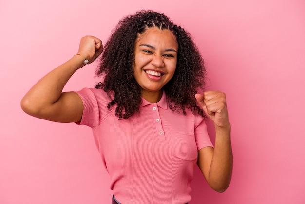 Giovane donna afroamericana isolata sulla parete rosa ballando e divertendosi
