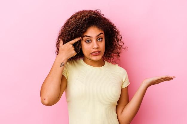 Giovane donna afroamericana isolata sul muro rosa che tiene e che mostra un prodotto a portata di mano.