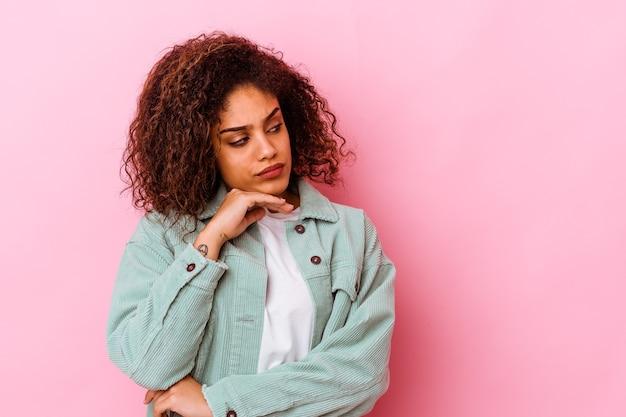 Giovane donna afroamericana isolata sulla parete rosa che osserva obliquamente con espressione dubbiosa e scettica.