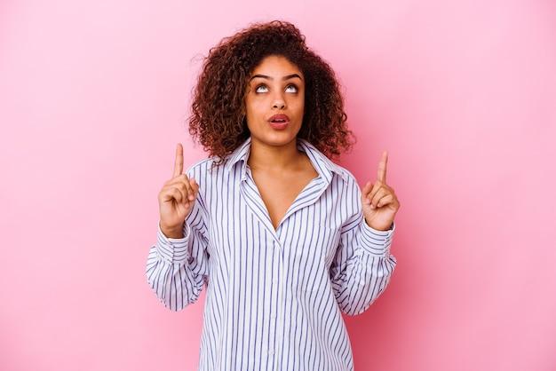Giovane donna afroamericana isolata sulla parete rosa rivolta verso l'alto con la bocca aperta.