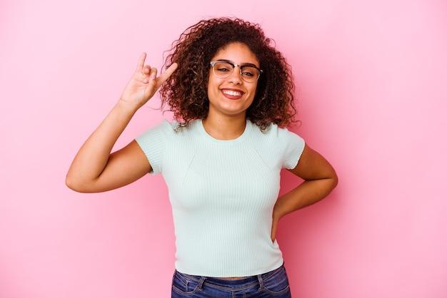 Giovane donna afroamericana isolata sulla parete rosa che mostra il gesto della roccia con le dita