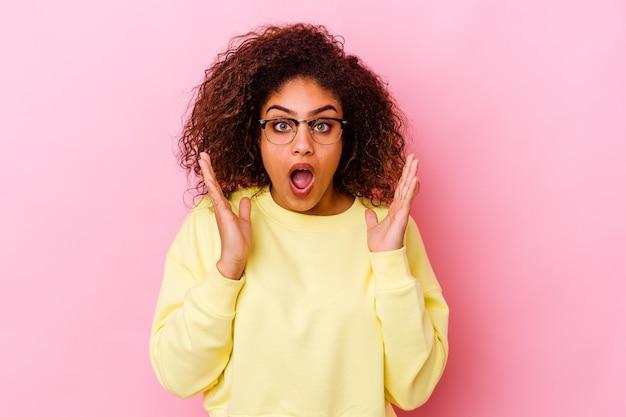 Giovane donna afroamericana isolata sulla parete rosa sorpresa e scioccata