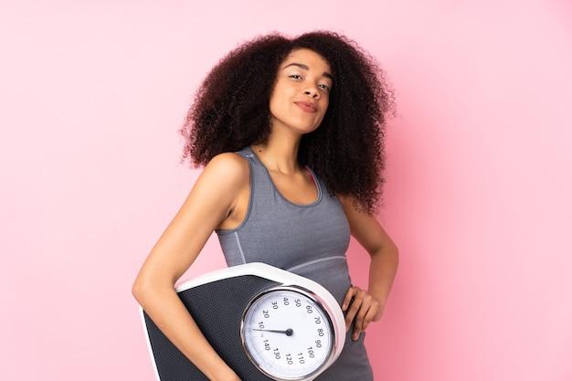 Giovane donna afro-americana isolata sul rosa con le braccia all'anca e tenendo la macchina per pesare