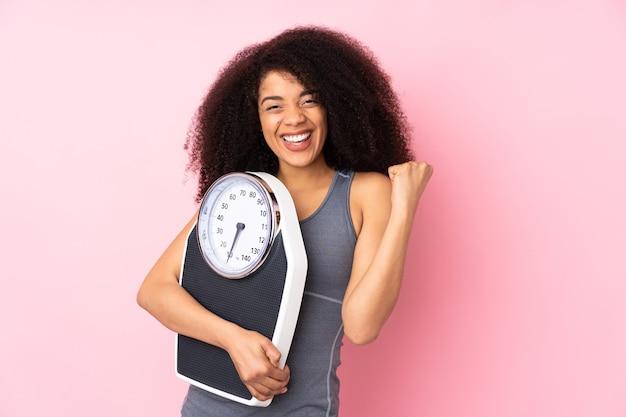 Giovane donna afroamericana isolata sul rosa con macchina di pesatura e facendo il gesto di vittoria