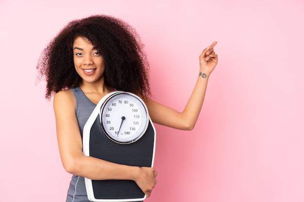 Giovane donna afroamericana isolata sul rosa con bilancia e lato di puntamento