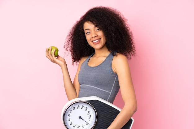 Giovane donna afroamericana isolata sul rosa con macchina per pesare e con una mela