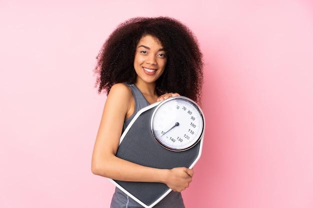Giovane donna afroamericana isolata sul rosa con la pesa