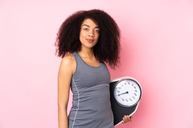 Giovane donna afroamericana isolata sul rosa con macchina per pesare