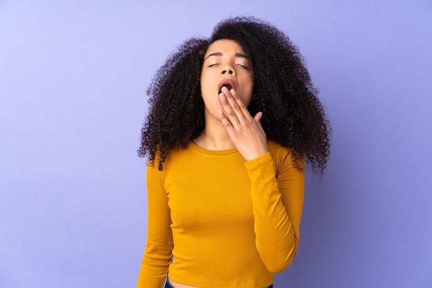 Giovane donna afro-americana isolata su viola che sbadiglia e coning bocca spalancata con la mano