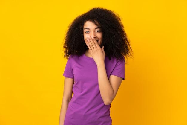 La giovane donna afroamericana sopra la parete isolata felice e sorridente copre la bocca con la mano