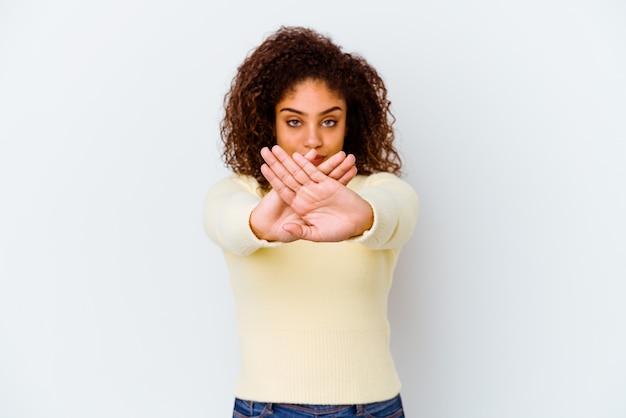 Giovane donna afroamericana isolata su fondo bianco che fa un gesto di rifiuto
