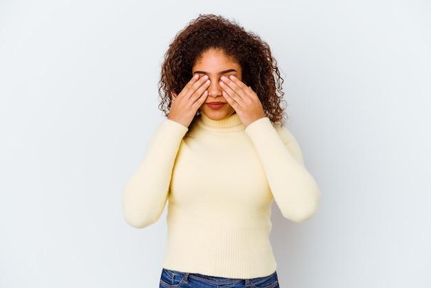 Giovane donna afro-americana isolata sul muro bianco paura che copre gli occhi con le mani.