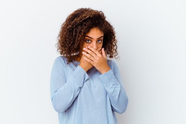 Giovane donna afroamericana isolata sulla bocca bianca del rivestimento murale con le mani che sembrano preoccupate.