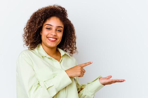 Giovane donna afroamericana isolata sulla parete bianca eccitata che tiene uno spazio della copia sul palmo