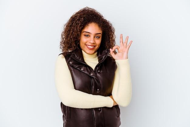 La giovane donna afroamericana isolata sul muro bianco strizza l'occhio e tiene un gesto giusto con la mano.