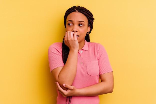 Giovane donna afro-americana isolata su sfondo giallo unghie mordaci, nervose e molto ansiose.