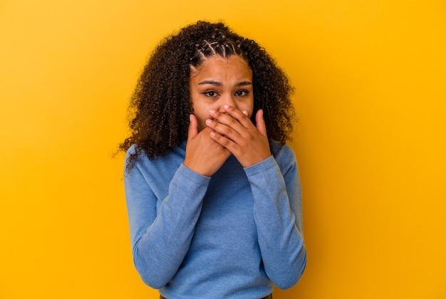Giovane donna afroamericana isolata su fondo giallo che copre la bocca con le mani che sembrano preoccupate.