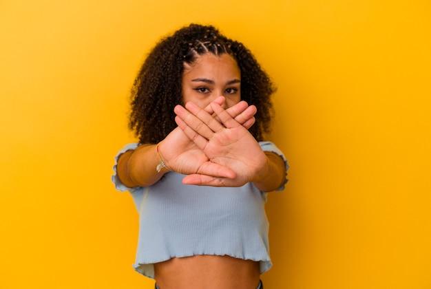 Giovane donna afroamericana isolata su fondo giallo che fa un gesto di rifiuto