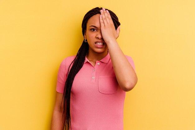 Giovane donna afro-americana isolata su sfondo giallo dimenticando qualcosa, schiaffi sulla fronte con il palmo e chiudendo gli occhi.