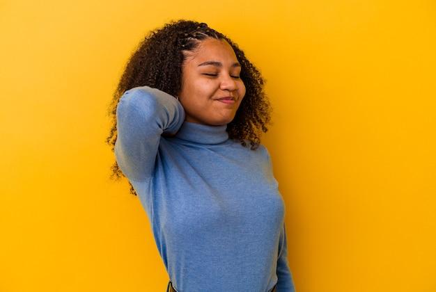 Giovane donna afroamericana isolata su sfondo giallo con dolore al collo dovuto allo stress, massaggiandolo e toccandolo con la mano.