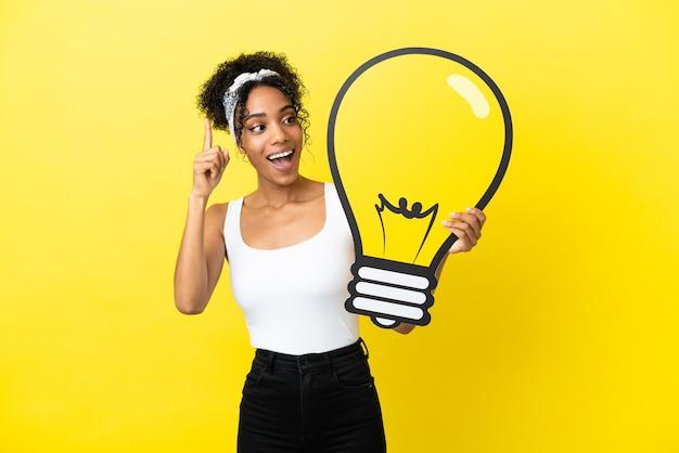Giovane donna afroamericana isolata su fondo giallo che tiene un'icona della lampadina e che pensa
