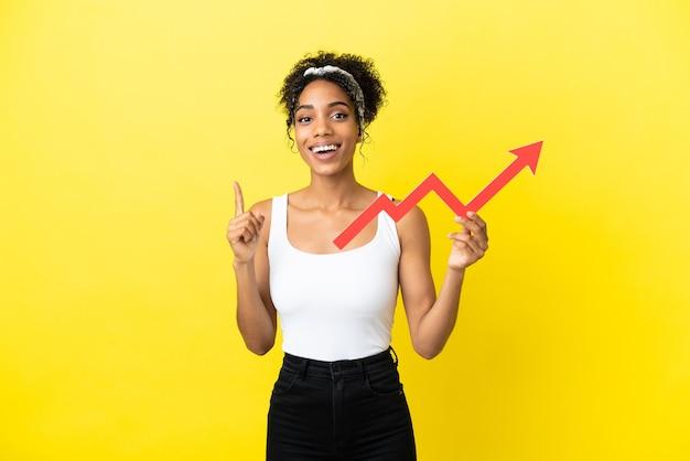 Giovane donna afroamericana isolata su fondo giallo che tiene una freccia che si alza e che indica su