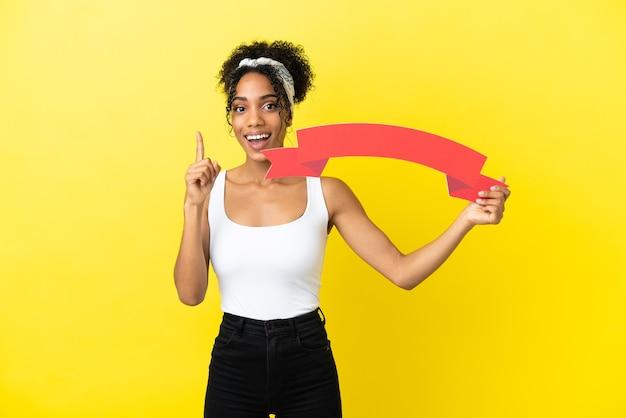 Giovane donna afroamericana isolata su fondo giallo che tiene un cartello vuoto e che indica su