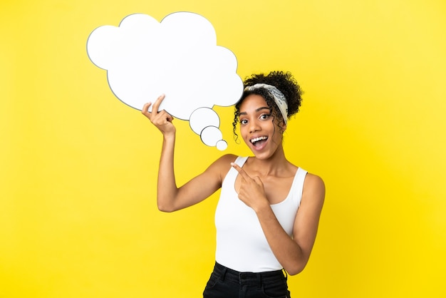 Giovane donna afroamericana isolata su fondo giallo che tiene un fumetto di pensiero con espressione sorpresa