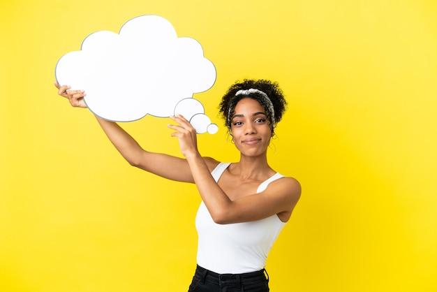 Giovane donna afroamericana isolata su fondo giallo che tiene un fumetto di pensiero
