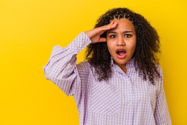 Giovane donna afroamericana isolata su sfondo giallo che guarda lontano tenendo la mano sulla fronte.