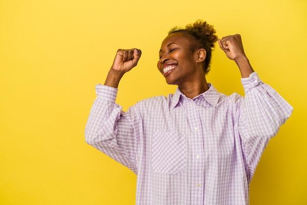 Giovane donna afroamericana isolata su fondo giallo che alza il pugno dopo una vittoria, concetto del vincitore.